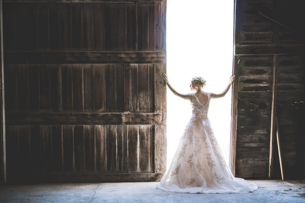 Bride opening barn doors for barn wedding near Scotts Bluff National Monument