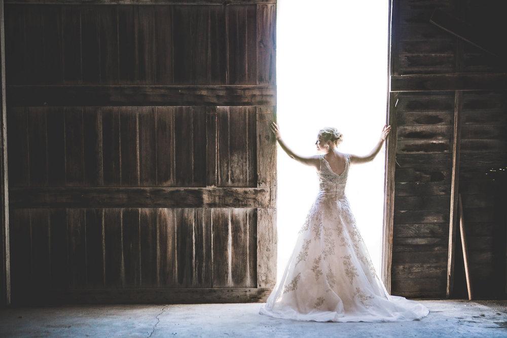 Bride opening barn doors for barn wedding near Scotts Bluff National Monument