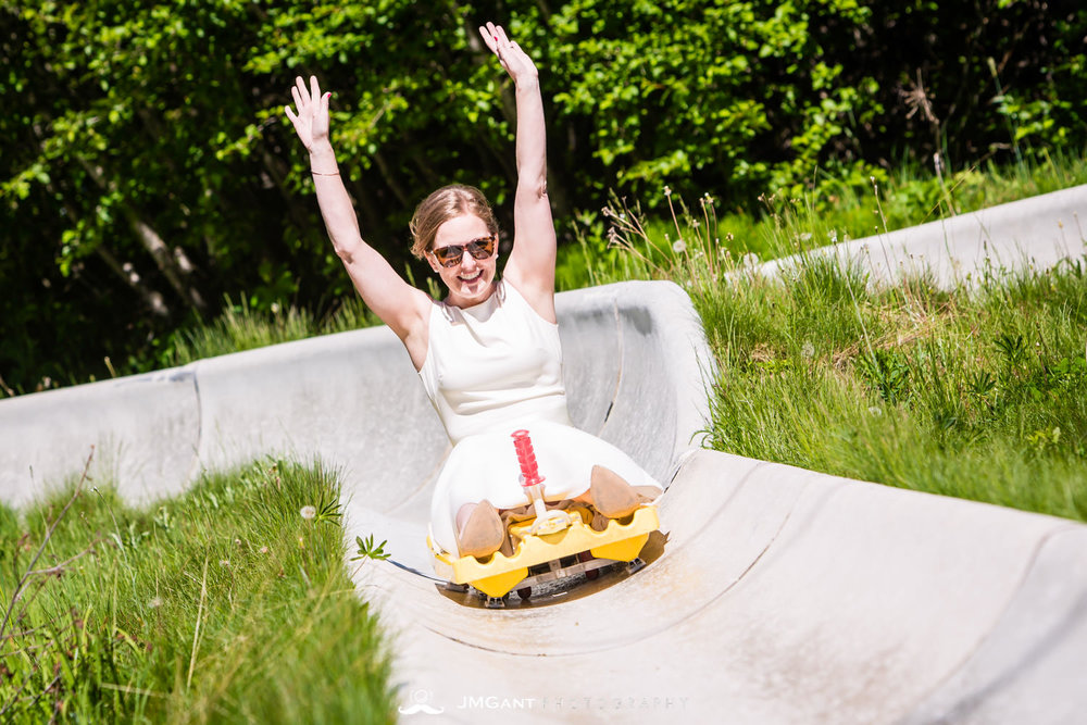 Bride and groom ride the Alpine Slide down at Winter Park, mountain wedding.