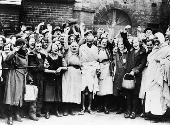 Gandhi has a laugh with millworkers in Darwen, Lancashire.