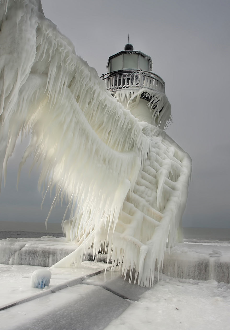 A lighthouse wears the remorseless winged cloak of winter