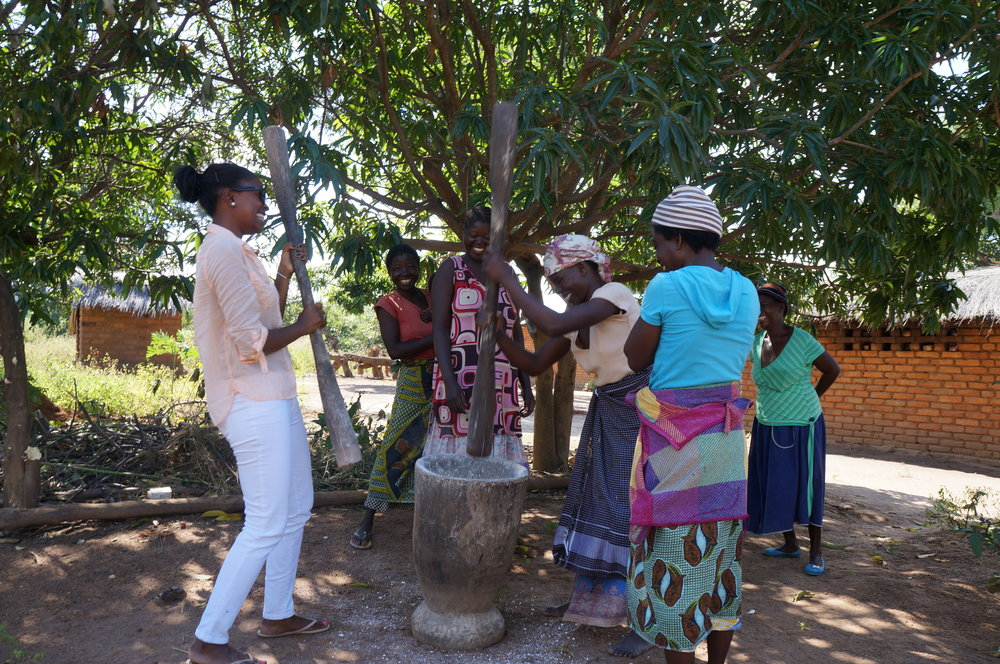 Nash doing a very mediocre job pounding cassava into flour for 'nsima', in her white jeans.  These ladies and I found it hilarious.