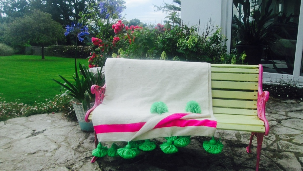 Here's a lovely pic of our wonderful Moroccan pom pom blanket in lime + fuchsia, looking good in this Devonshire garden. What came first... the bench or the blanket?.... a match made in Devon!