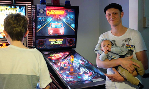 Andrew with son Oliver. One would expect Ollie to be a future pinball champion with the available in-house coach. Photo by Australian Pinball League.