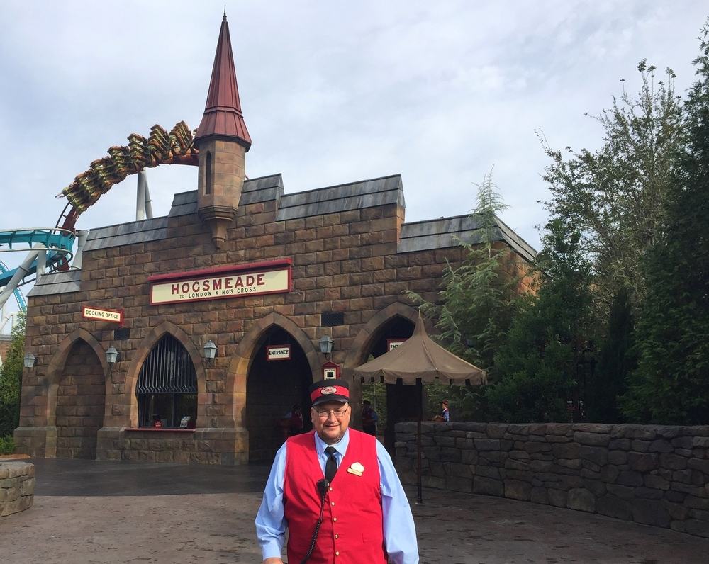 A conductor in front of Hogsmeade station. You can see riders on Dragon Challenge in the background.