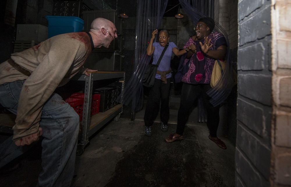 HHN guests getting a scare in the Walking Dead House during HHN 25. Image credit: Universal Orlando Resort.