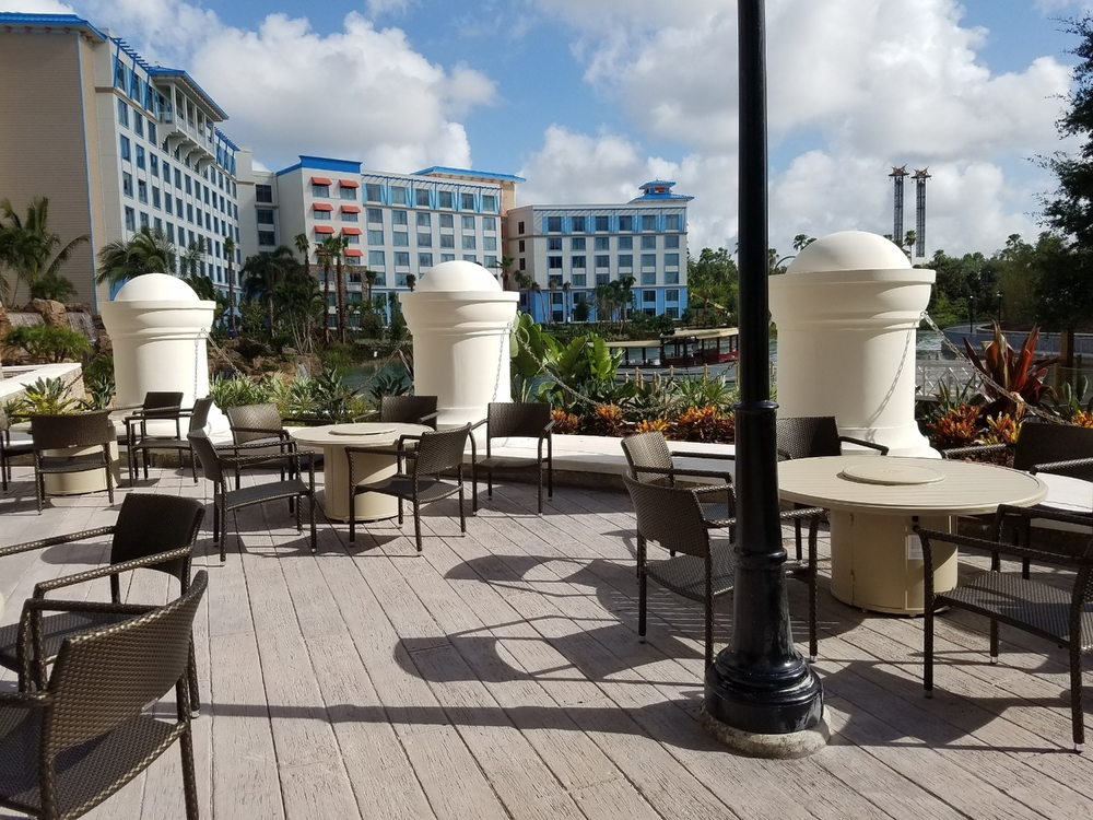 Outdoor patio overlooking the water taxi dock at Loews Sapphire Falls Resort. The patio contains chairs and small tables with built-in fire pits.
