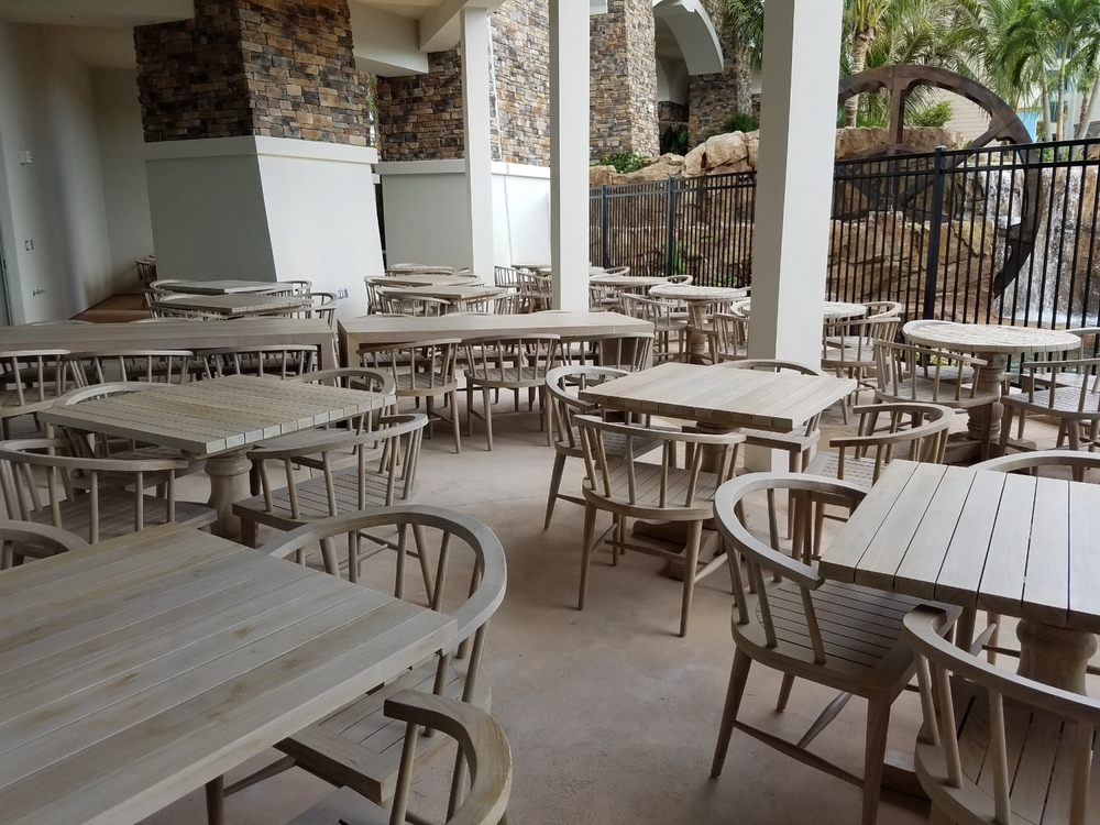 The outdoor seating area at  Amatista Cookhouse at Loews Sapphire Falls Resort. This seating area has a view of the water wheel, waterfalls, and the lagoon.