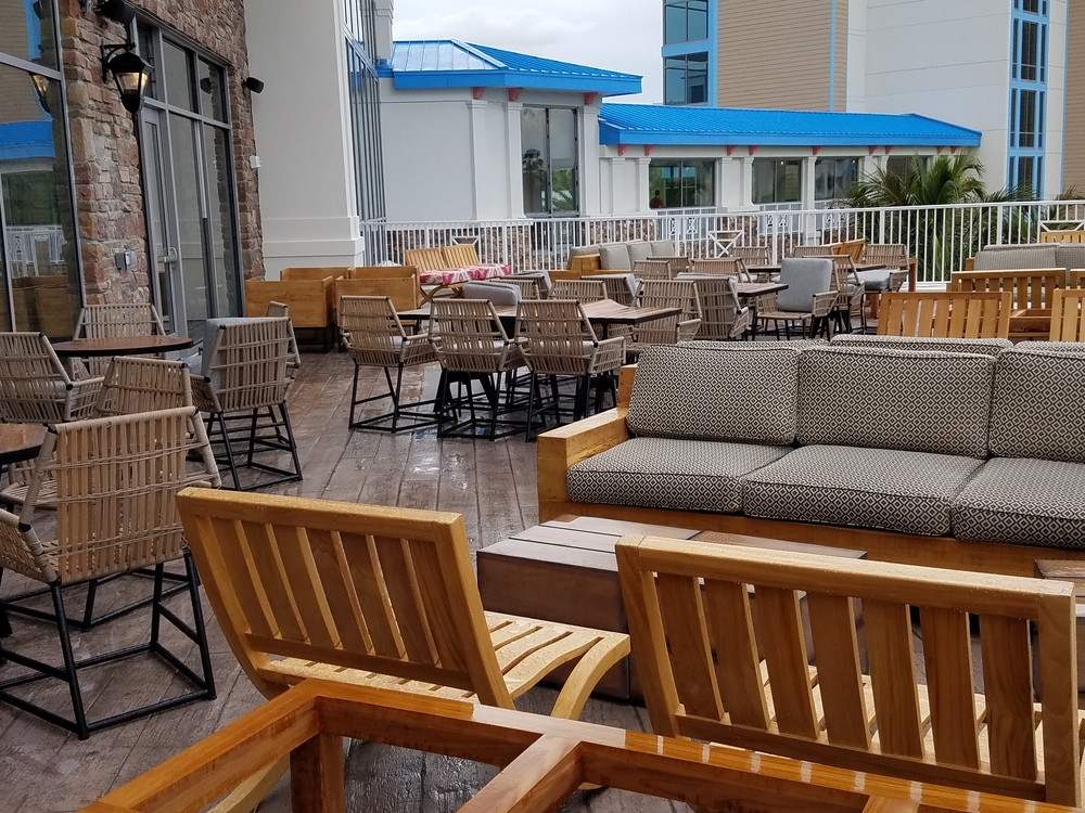 Outdoor seating area of Strong Water Tavern at Loews Sapphire Falls Resort. This patio is not covered.