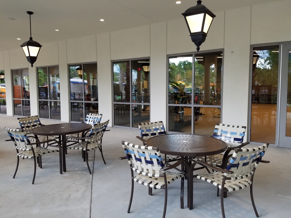 Tables and chairs on a covered patio near the pool at Loews Sapphire Falls Resort. The fitness center is on the other side of the windows.