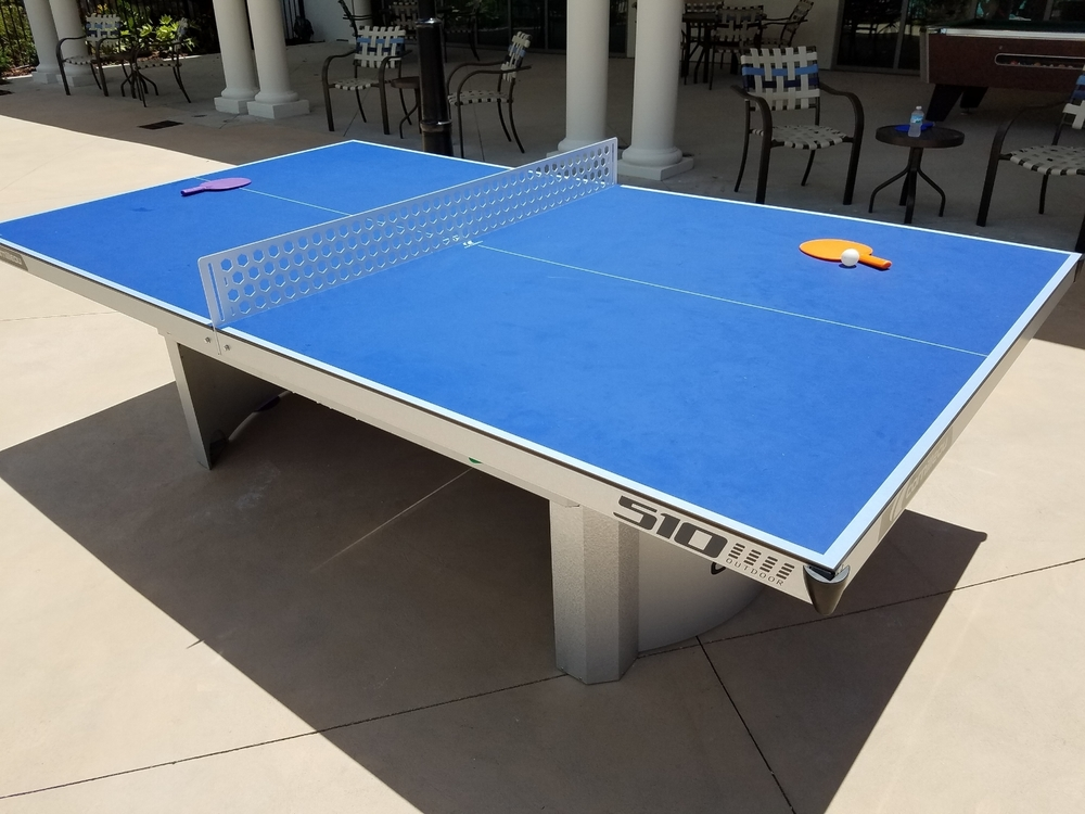 The ping pong table is on an outdoor patio near the pool at Loews Sapphire Falls Resort. You'll also find a pool table, hula hoops, cornhole games, and more in this area.