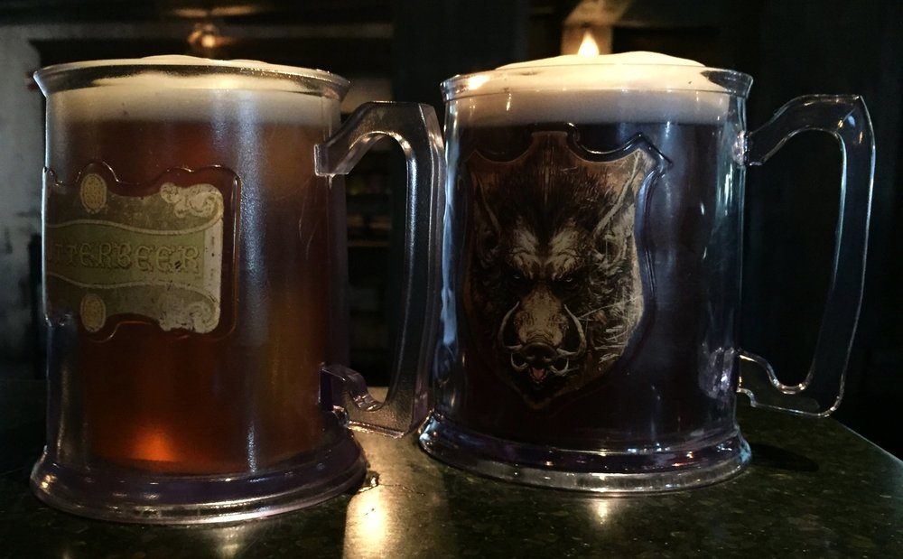 You can order your Butterbeer from Three Broomsticks in souvenir mugs. One mug features the Butterbeer logo, and the other mug features the Hog's Head logo.
