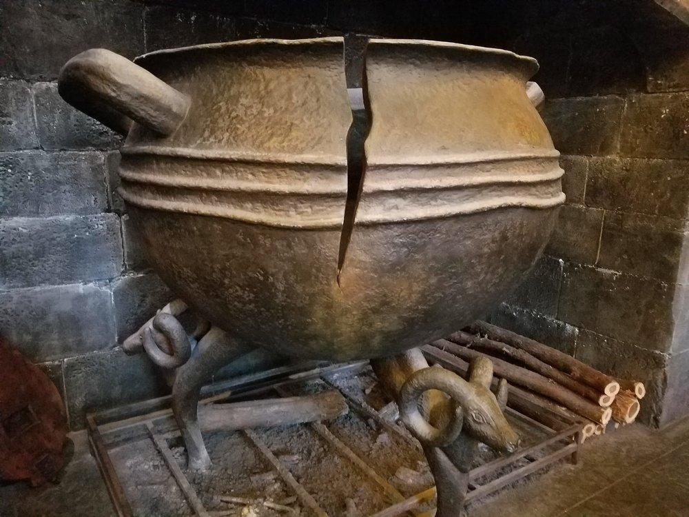 The cracked cauldron in the hearth at the Leaky Cauldron.