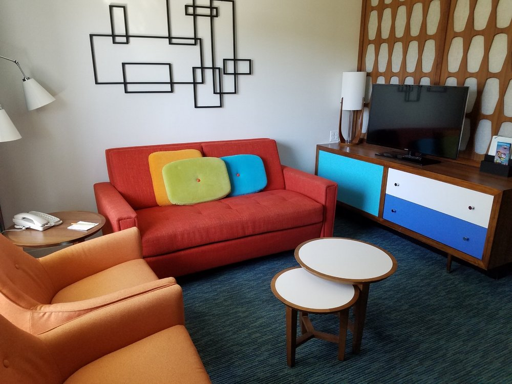 The living area of the family suite at Universal's Cabana Bay Beach Resort has a TV and seating for multiple people. The couch folds out into a bed that can sleep up to two people.