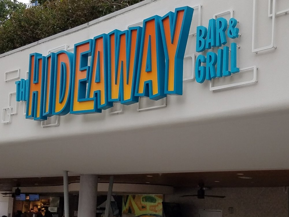 The Hideaway Bar and Grill is located near the Lazy River pool at Universal's Cabana Bay Beach Resort. The menu features appetizers, salads, sandwiches, wraps, burgers, desserts, and beverages.