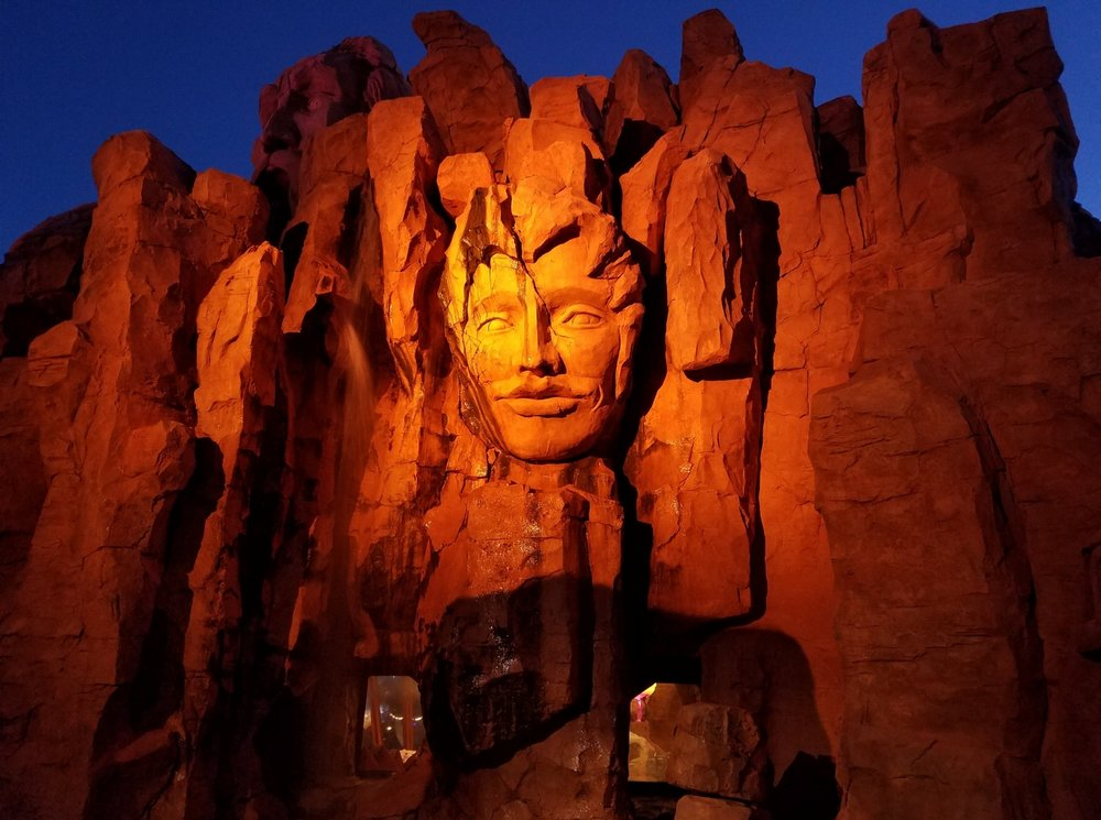Part of the Mythos Restaurant exterior at night.