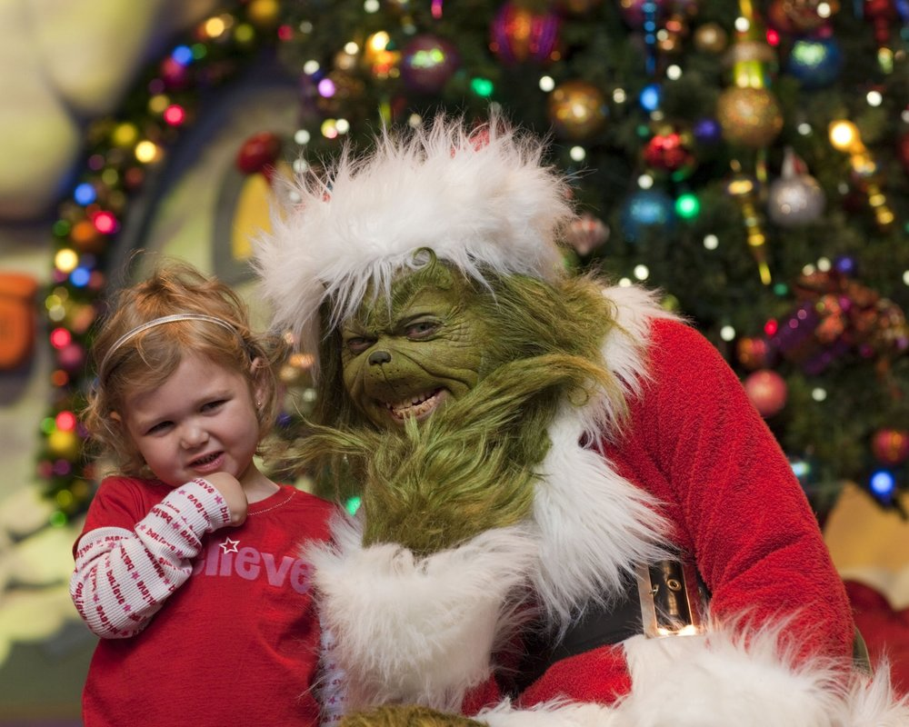 The Grinch meeting a young guest at Universal during the holidays. Image credit: Universal Orlando Resort.