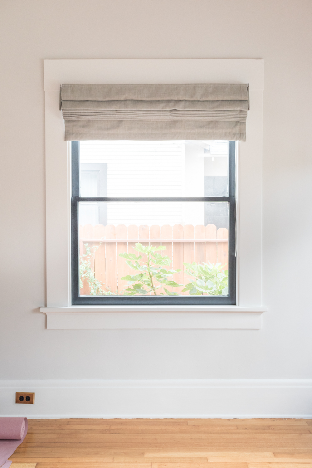 roman shade on window with black sash and white trim