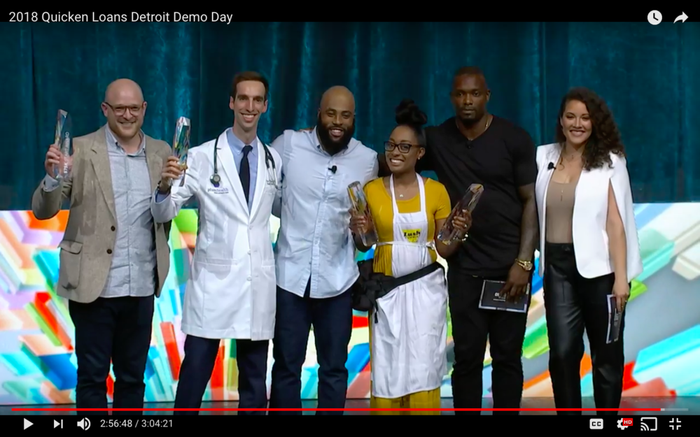 "Screenshot from Quicken Loans Detroit Demo Day video - winners from the ""Start"" category including Justin Mast of Bloomscape with a $75,000 prize, Paul Thomas MD of Plum Health DPC with a $50,000 prize, James Chapman (host), Jennifer Lyle of Lush Yummies Pie Co with the $25,000 People's Choice Award and the $100,000 prize, Ron Bartell of Kuzzo's Chicken and Waffles and former Detroit Lion (judge), and Janelle Bechdol of The Hall Pass Tour (host). Judges not pictured here are Anne Sempowski Ward a Detroit native and CEO of CURiO brands and Charles Adler the Co-founder of Kickstarter."