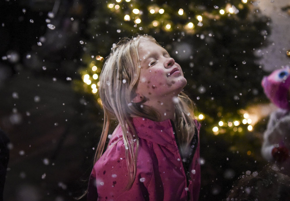 Serena Brown, 8, closes her eyes as snowflakes from a snow machine fall on her face at Activate Church's sixth annual Christmas at the Park in Esther Short Park, Friday evening December 1, 2017. (Ariane Kunze/The Columbian)