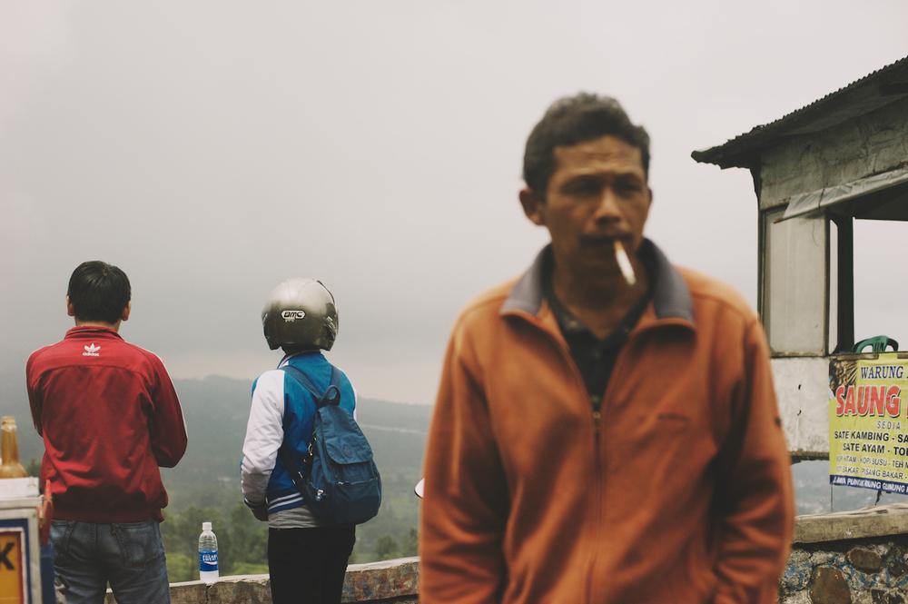 indonesian man smoking top of the puncak pass indonesia