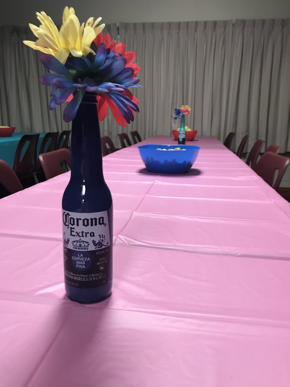 table decor including DIY painted Corona bottles with dollar store florals.