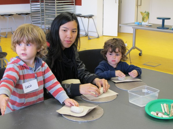 This image shows a teacher actively engaged in young children's exploration of paper clay