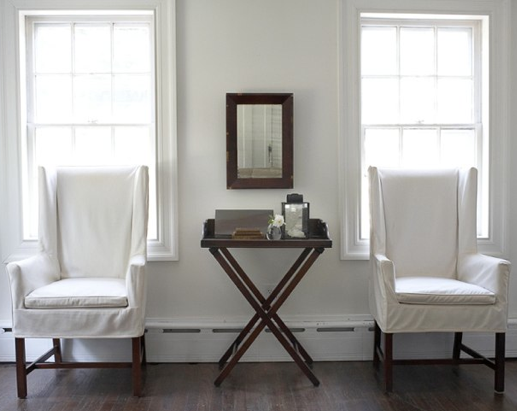 Wood, white walls, slipcovers and plain windows.  This shows such restraint.  I must remember this the next time I feel compelled to add a pillow!