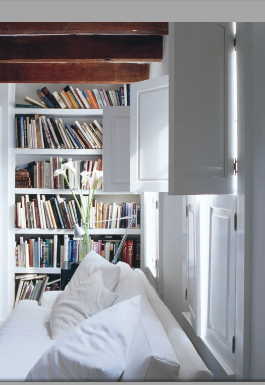Linen sofa, a jumble of books on simple shelves, and the light entering into the room through the shutters- sigh.