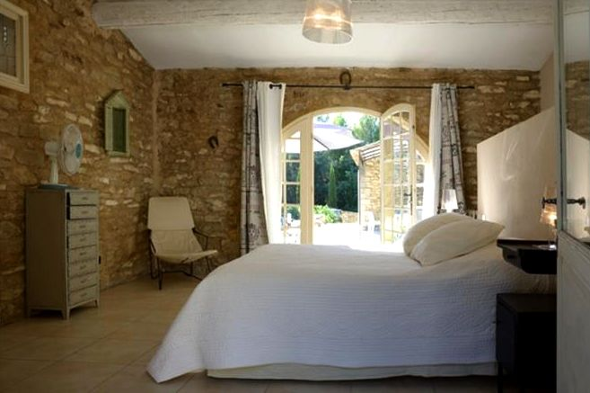 Real french doors opening to the pool and terrace. Love the rough stone walls and the matelasse coverlet.