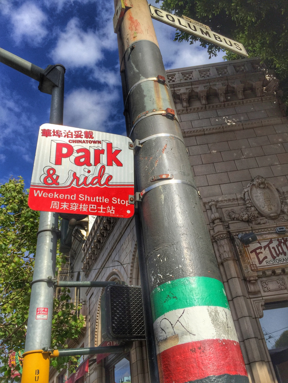A quintessential representation of blurred culture lines: an Italian flag and a Chinese/English bilingual shuttle stop sign adorning the same pole