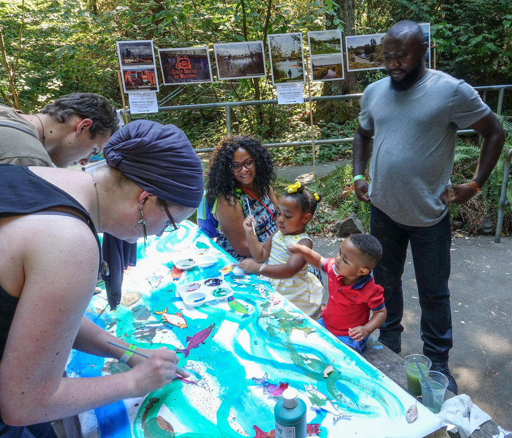 Families and young adults participating in creating a river full of colorful salmon at the Arts in Nature Festival.
