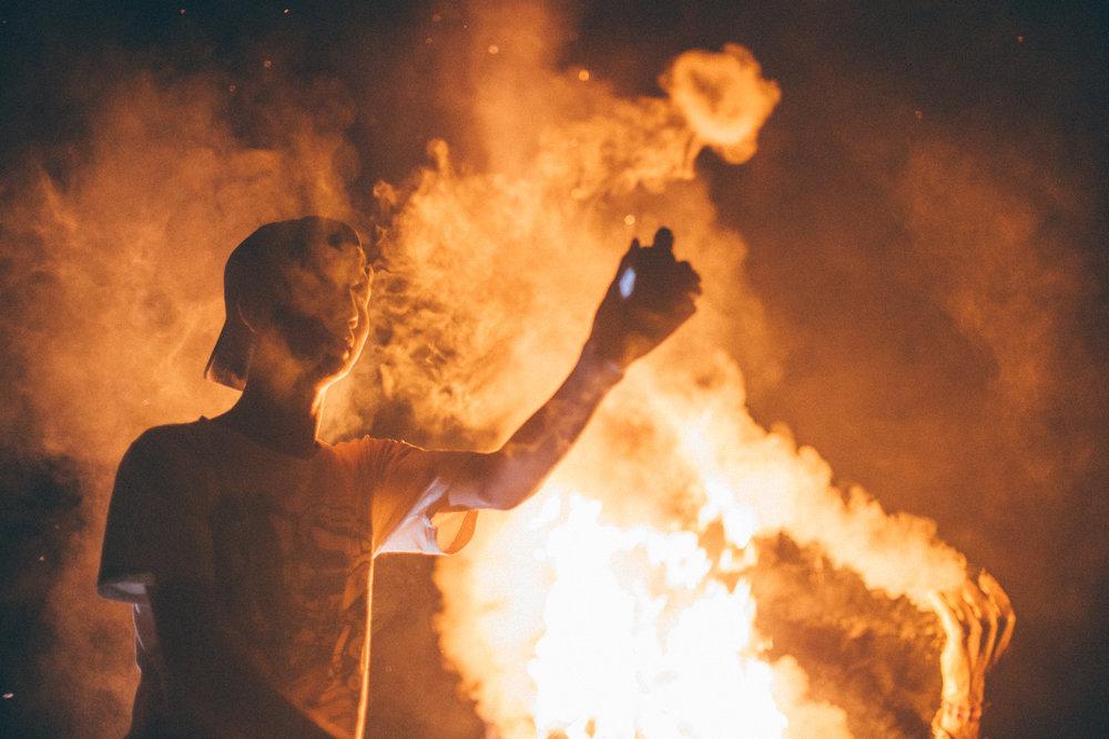 A Balinese teenager blows vape rings at an  ogoh ogoh  burning.