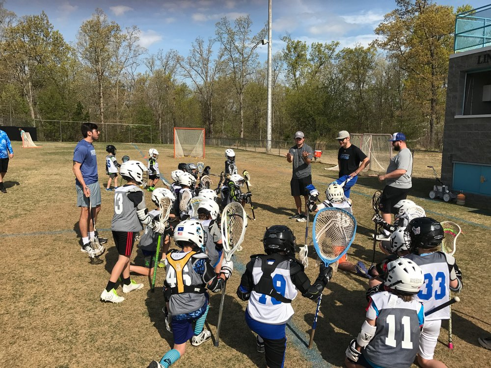 Coaches, Joey Porchetta, Joe Cummings, Matt Hogue, and Matt Hastings teach a group of 4th grade boys before a game.