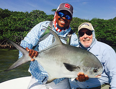 Fly Fishing guide with his client and a big permit caught in Belize