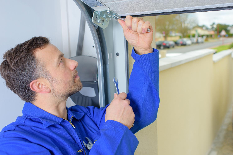 Repair trotter garage home bigstock man installing a garage door 90007880g rubansaba