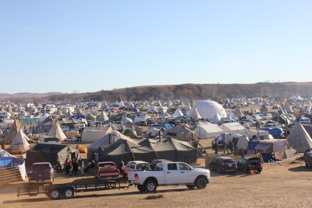 Teepees, canvas tents, RVs, yurts, corrals, moving vans, and adapted buses pepper the camp known as Oceti Sakowin. The white geodesic dome is a donation from Burning Man, and serves as a communal space for meals, orientation meetings, action meetings, and a nightly discussion of decolonization. It also provides sleeping space for campers unprepared for cold weather.