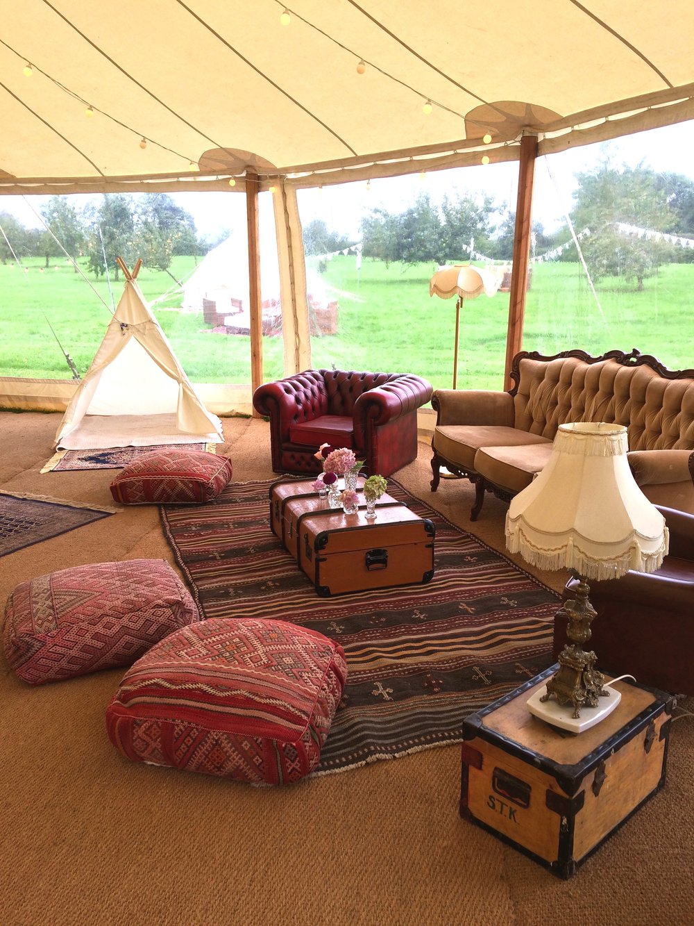 Inside the lovely pole marquee we created a chill out space that reflected an Englishman's study with a touch of Constantinople. Travel trunks for tables and traditional standard lamps, Chesterfields, wing armchairs and Berber poufs.