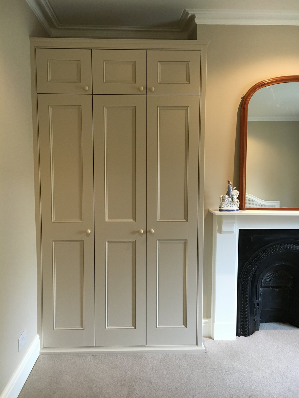 Panelled doors with smaller linen cupboard above.
