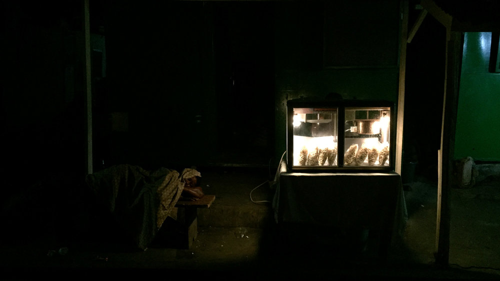 A popcorn seller sleeps beside her shop across from our bar. 4am on saturday night.