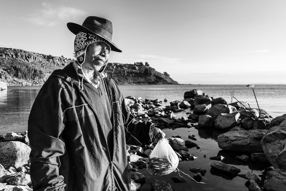 A man of Amantani buys fresh fish everyday at sunrise from the fishermen who just returned with daily catch. Intensive fishing has deprived the lake's waters, leaving nothing but endemic killifish.