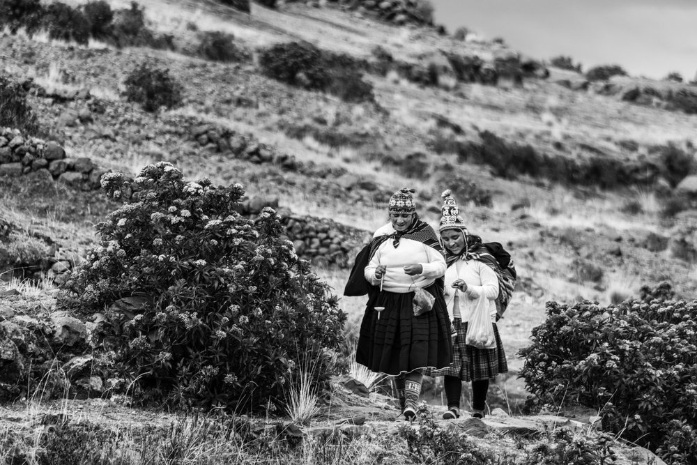 A couple of women are climbing the hills of Amantani island to reach the ruins of  Pachatata . There, they will hopefully sell handicrafts to the tourists who visit the island.