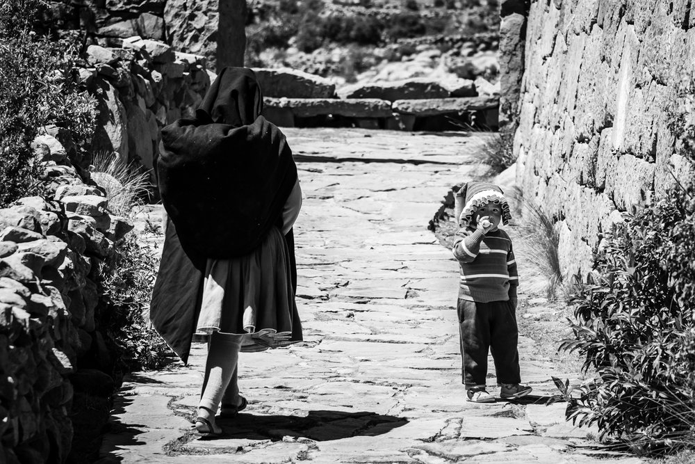 A little kid and her mother, walking on the narrow alleys of Taquile island on lake Titicaca. Young children are helping their families on the crop fields as well as by selling items to tourists.