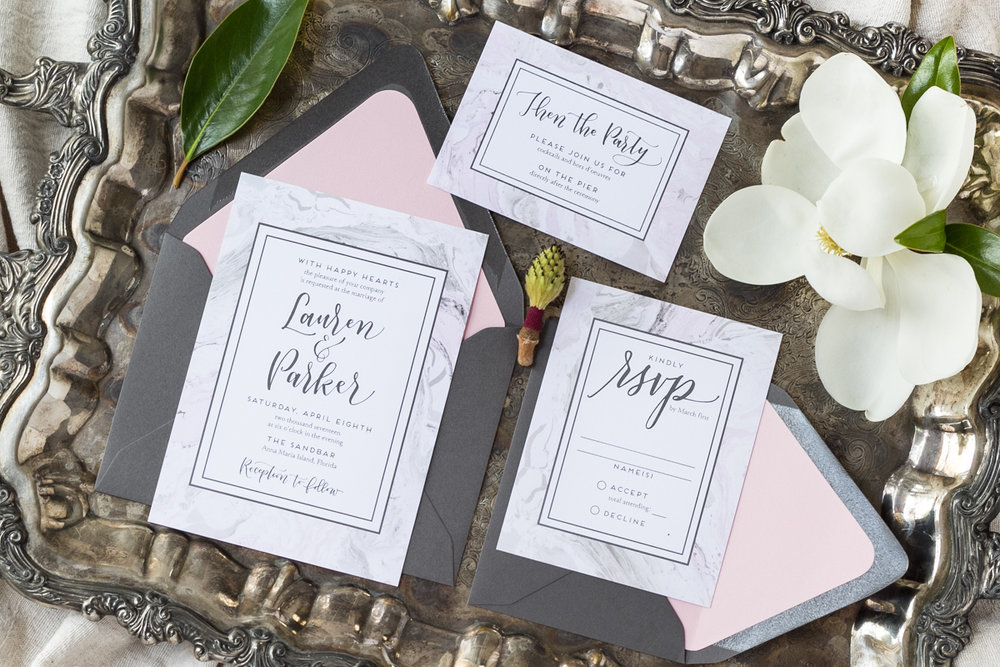 Hand lettered pink and grey wedding invitation on marble