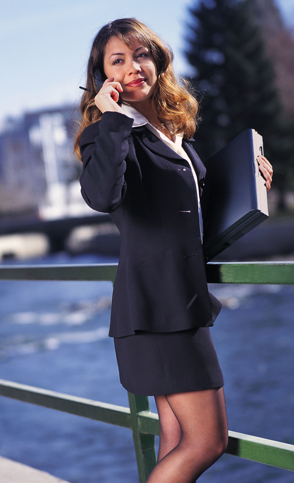 Businesswoman talking on cel holding laptop.jpg