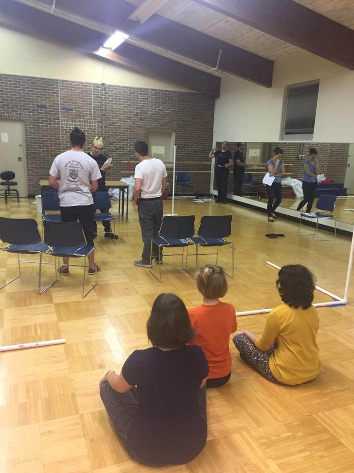 Macbeth (Chance Parker, center) hiring Banquo's murderers (Casey Stombaugh at left and Kevin Torwelle at right) as the three witches watch on (left to right: Sloan Amburgey-Thomas, Izzy Chilian, and Amber Albright). To the right of our makeshift stage, Nate Driscoll (Duncan) and Shelby Lewis (Lady Macbeth) practice lines by the mirrors.