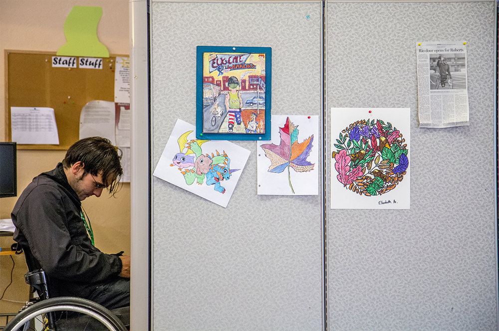 "John sits in his chair at his workplace on Thursday, Nov. 10. Five months ago on an average workday in June, John's phone rang. It was the USA Paralympic coach. ""You're going to get to represent your country,"" the coach told him. John immediately calls his mom and dad. It was the realization of a goal he had been working towards for twenty years. ""It was sort of a tearful moment, and something that I'll never forget,"" John said."