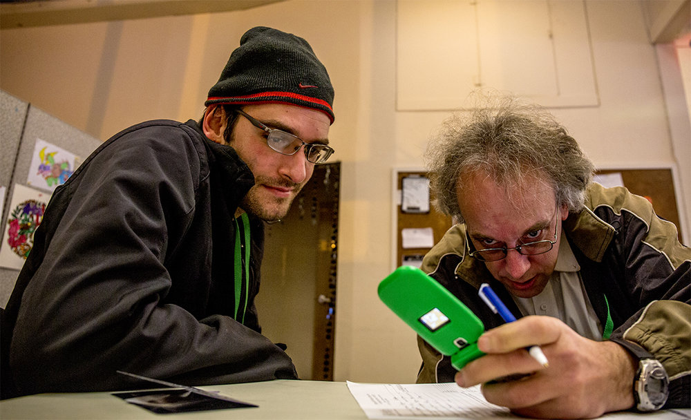 "John assists a frequenter of the Lila Support Club, Michael, in getting his paperwork together for a passport. Michael hopes to be able to travel around the States and hopefully abroad after that. ""I grew up in like a mid-western town where there weren't that many opportunities for people with disabilities, and then moving to Oregon kind of changed my whole outlook on life and just thinking about life beyond my disability,"" John said."