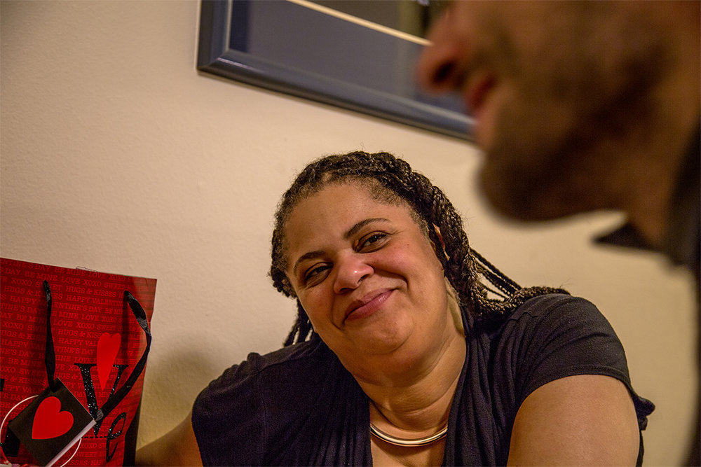 John's girlfriend Kiesha looks on at him during their Valentines Day dinner. The two have been together for nine months now. The first time he asked her out she said no, but when he came back several years later more mature she saw that and said yes. Kiesha describes how their families breathed a sigh of relief, having known it was inevitable.