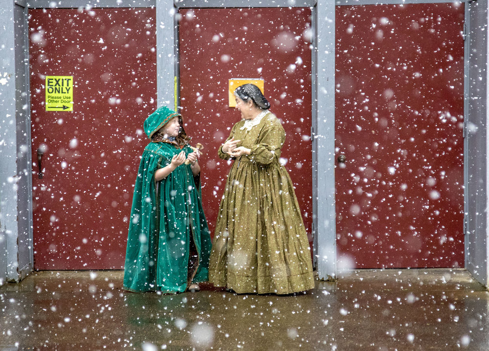 Hailey McKendrick, 7, and Lisa Ponder step outside the Frontier Heritage Fair to watch a rare snowfall in Eugene, Ore., on Sunday, Feb. 19, 2018. The Heritage Fair brought old fashioned clothing, art and tools to 21st century Eugene. Ponder attended the fair as part of the Pioneer Quilters, and with two other women demonstrated the art of quilting.